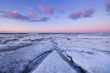Eis bedeckt das Wattenmeer im Winter an der Küste von Groningen bei Sonnenuntergang. Die untergehend von Bas Meelker