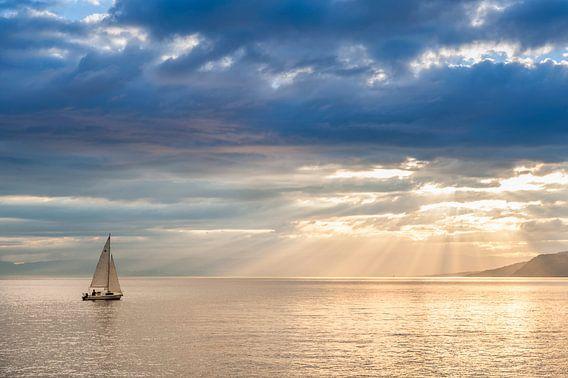 A small sailboat set sails on Leman lake (Switzerland).