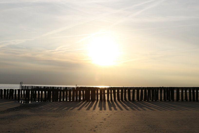 golfbrekers op het strand en zonsondergang van Frans Versteden