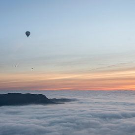 Three hot air balloons flying over a sea of clouds during sunrise. van Carlos Charlez