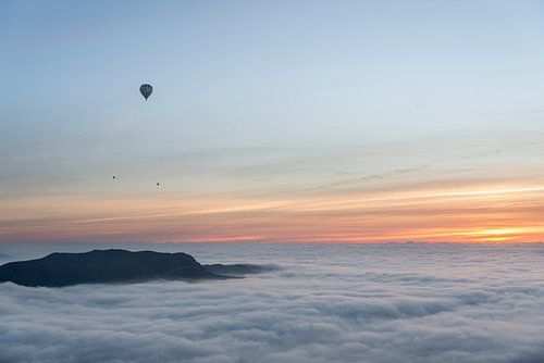 Three hot air balloons flying over a sea of clouds during sunrise. van