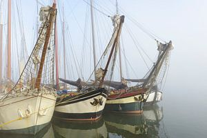 Oude zeilschepen aan de kade in Kampen in de mist