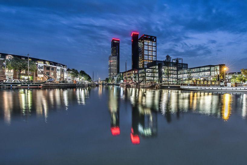 De skyline van Leeuwarden tijdens het blauwe uurtje en weerspiegeld in de stadsgracht. van Harrie Muis