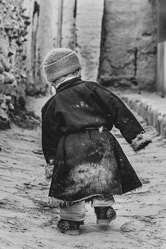 Kleine jongen wandelt door een straat