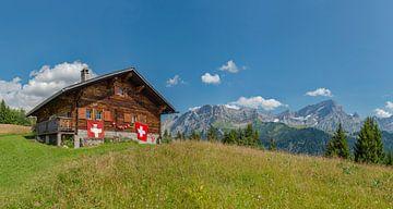 Berghut versierd met zwitserse vlaggen, Villars-sur-Ollon, Vaud, Zwitserland van Rene van der Meer
