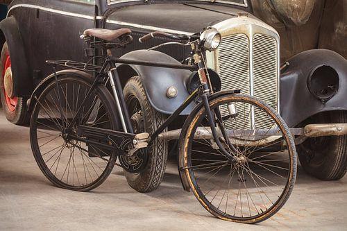 Antieke fiets en auto in een schuur van